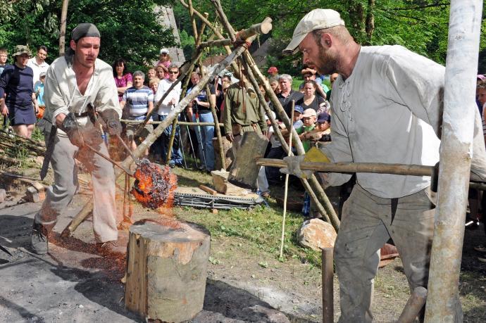Z pece právě vylomená železná houba bude kována na dřevěném špalku