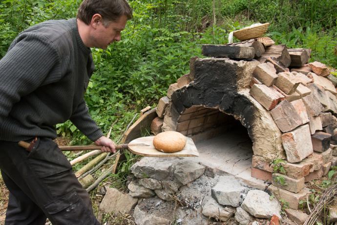 Autor vytahuje první, ještě lehce světlý chleba z pece
